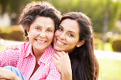 Mother With Adult Daughter In Park Together Smiling To Camera