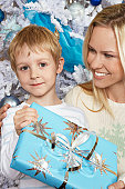 Mother with arm around boy (5-6) holding Christmas present