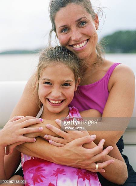 Mother with arms around daughter (8-10), portrait