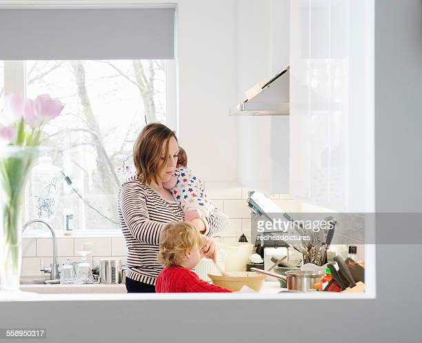 Mother with baby and toddler in kitchen