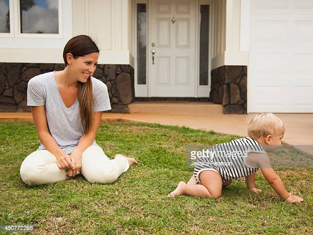 Mother with baby boy (6-11 months) in front of house