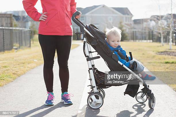Mother with baby boy in stroller on street