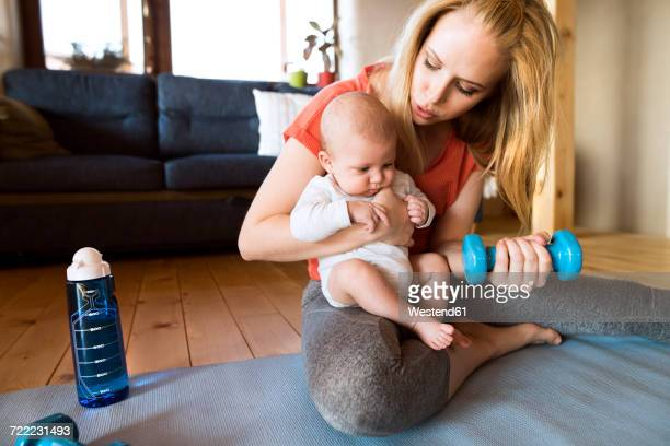 Mother with baby exercising with dumbbell at home