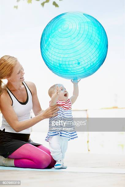 Mother with baby girl playing fitness ball