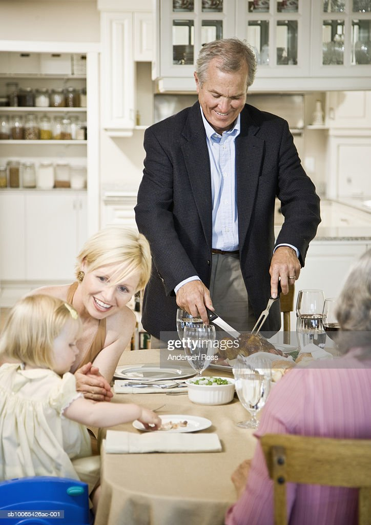 Mother with baby girl (9-12 months) while grandfather carves turkey : Stock Photo