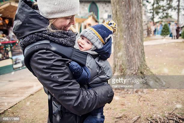 Madre con il neonato nel vettore diverte prima neve parco pubblico.