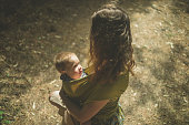 A young mother with her baby in a sling is standing in the clearing of a forest on a sunny day