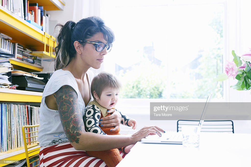 mother with baby in lap working on laptop at home : Stock Photo