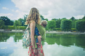 A young mother with her baby in a sling is walking by a pond in the park