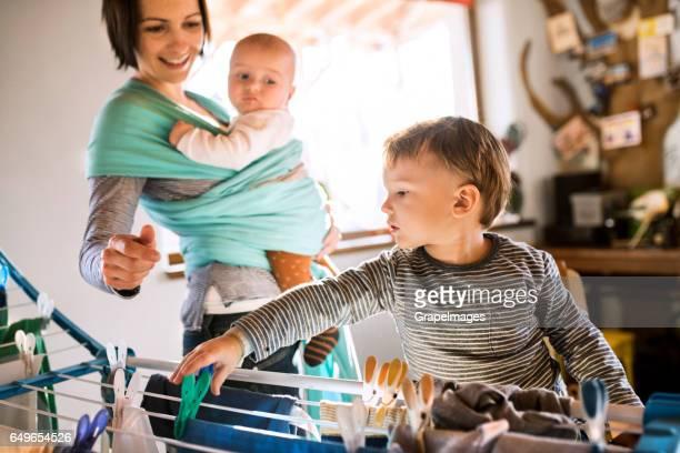 Mutter mit Baby im Tragetuch, Sohn, ihr zu helfen, mit Wäsche