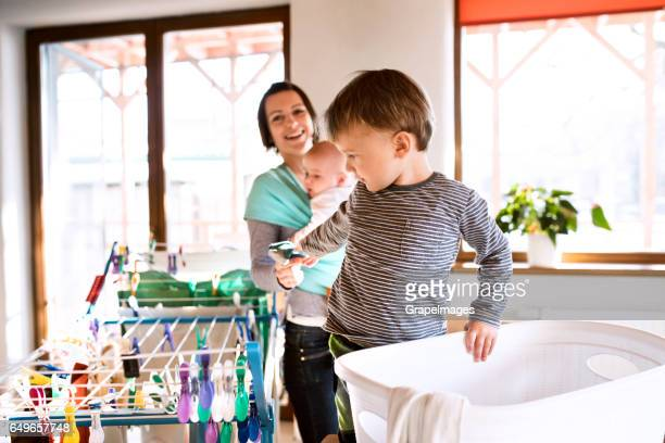 Mother with baby in sling, son helping her with laundry