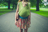 A young mother with a baby in a sling is walking in the park