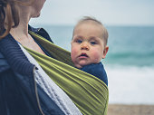 A mother is on the beach with her baby in a sling