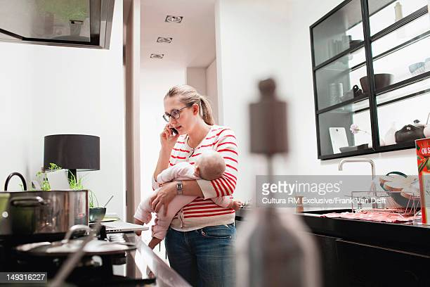 Mother with baby talking on cell phone