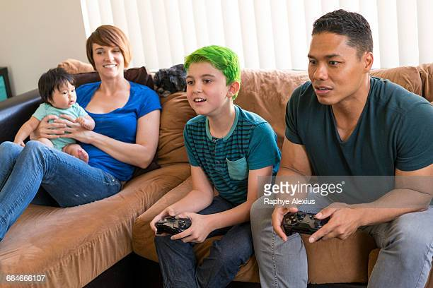 Mother with baby watching father and son playing video game on sofa
