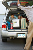Mother with boy and girl (8-13 years) in car, father closing boot lid