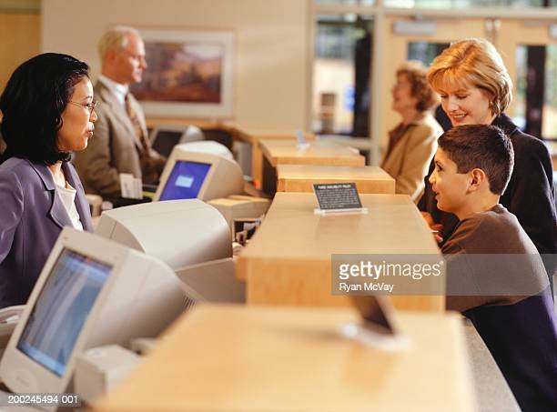 Mother with boy (14-15) talking with bank clerk at counter