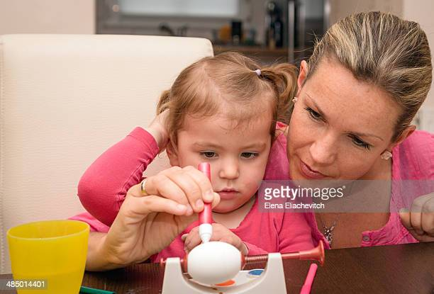 Mother with child painting Easter egg