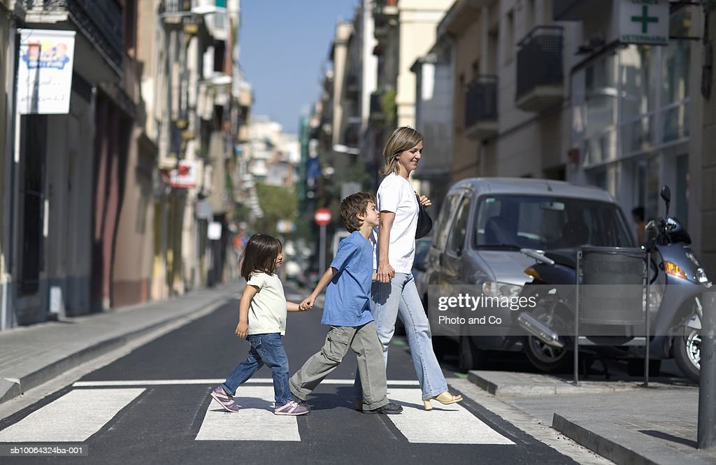 Mother with children (3-7) crossing street, side view : Stock Photo