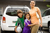 Mother with children (6-10) dressed in soccer uniforms