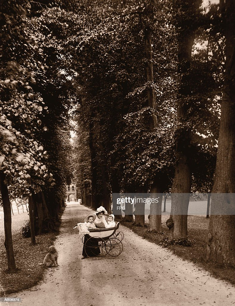 Mother with children (6-24 months) in carriage on path (B&W sepia) : Stock Photo