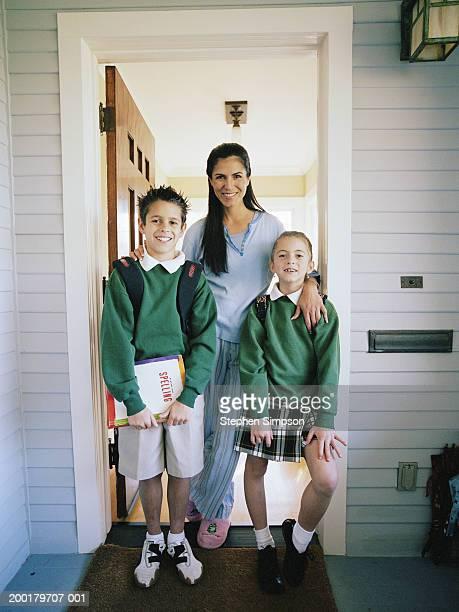 Mother with children (6-12) in school uniforms standing in doorway
