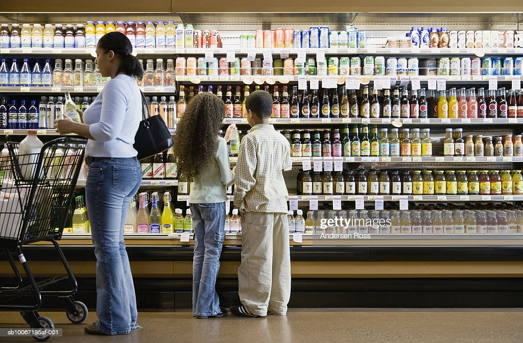Mother with children (8-11) in supermarket : Stock Photo