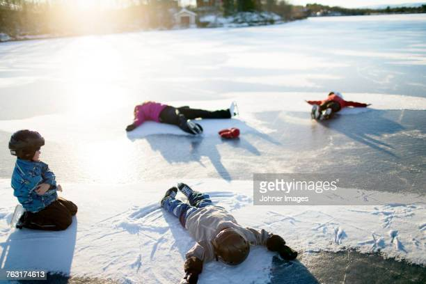 Mother with children making snow angels on frozen lake