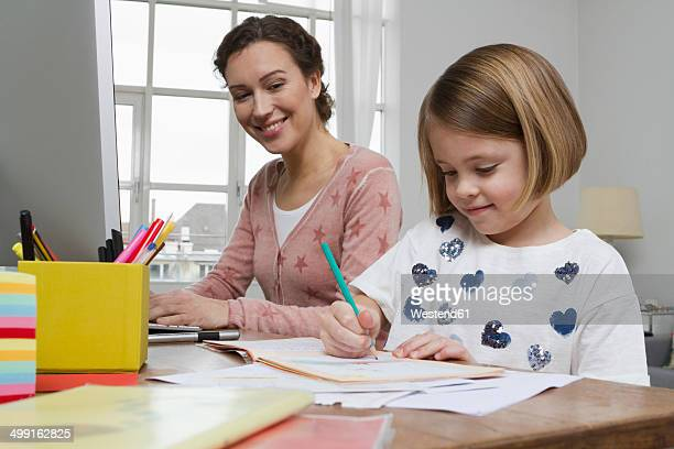 Mother with daughter at desk drawing