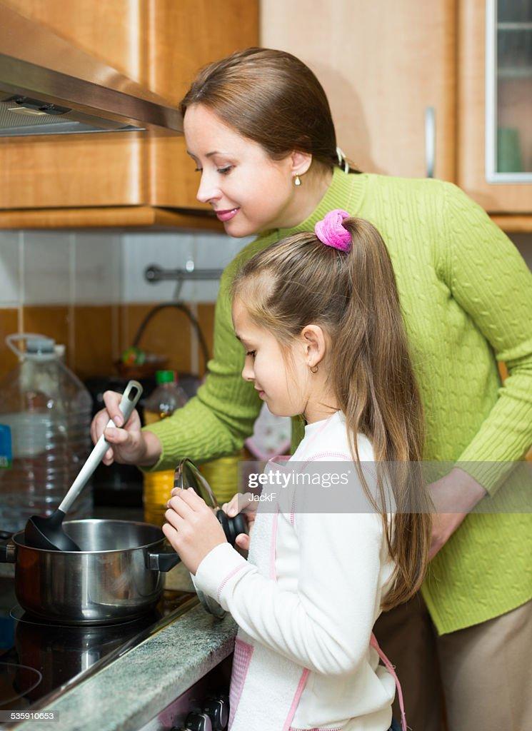 Mãe com filha a cozinhar na cozinha : Foto de stock