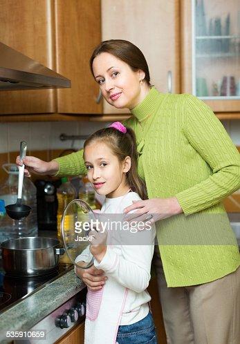 Madre con hija cocinar en la cocina : Foto de stock