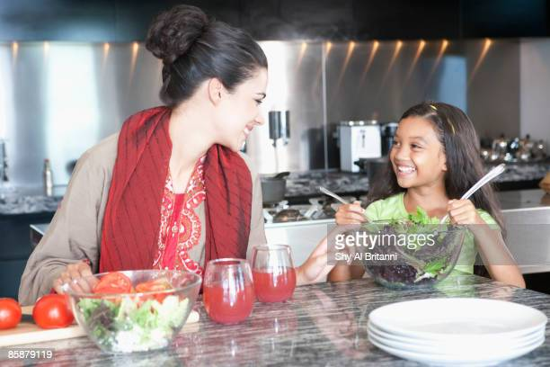 Mother with daughter cooking in kitchen.
