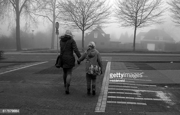 Mãe com menina atravessando a rua