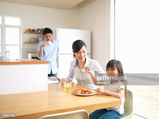 Mother with daughter (6-7) eating fruit in kitchen, father in background