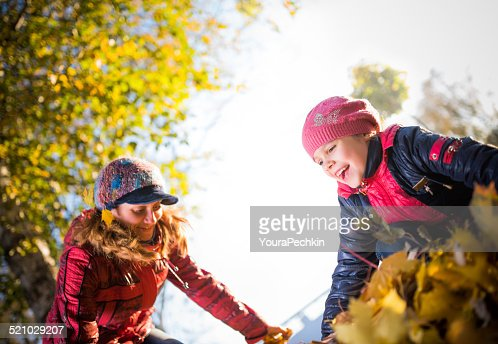 Mother with daughter fooling around in the foliage