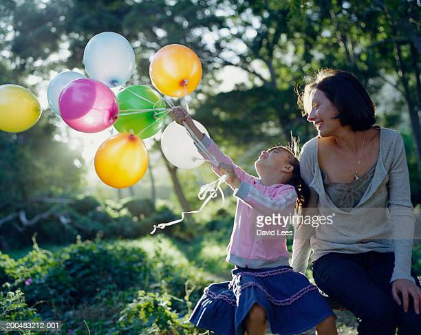 Mother with daughter (6-7) holding balloons sitting in garden