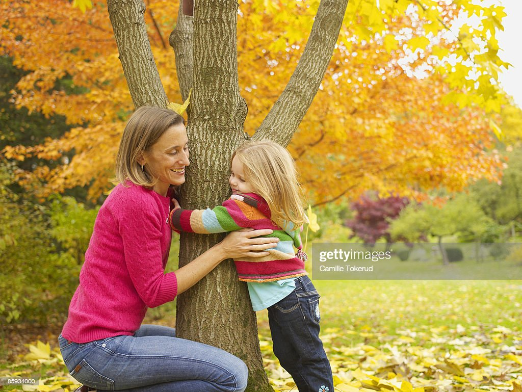 Mother with daughter hugging a tree, Autumn : Stock Photo