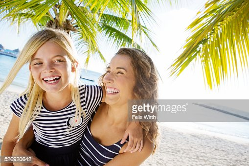 Mother with daughter (10-11) laughing on beach : Stockfoto