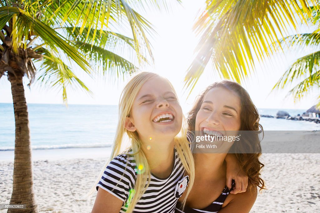 Mother with daughter (10-11) laughing on beach : Bildbanksbilder