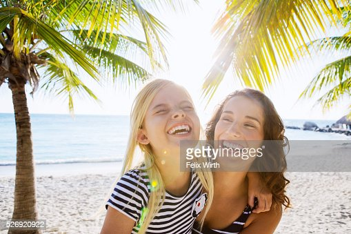 Mother with daughter (10-11) laughing on beach : Stock Photo