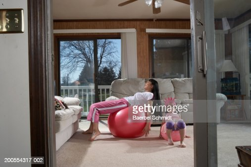 Mother with daughter (4-5) lying on exercise ball : Stock Photo