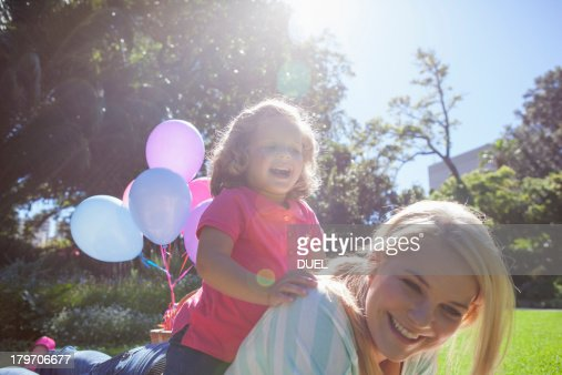 Mother with daughter lying on top in garden : Stock Photo
