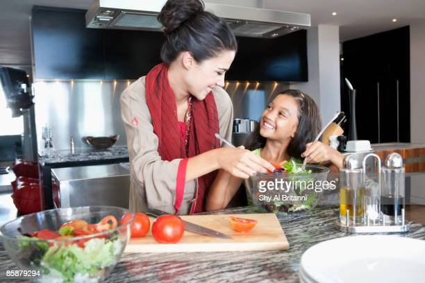 Mother with daughter mixing salad in bowl.
