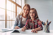 Attractive young woman and her little cute daughter are sitting at the table and doing homework together. Mother helps daughter with her school classes.