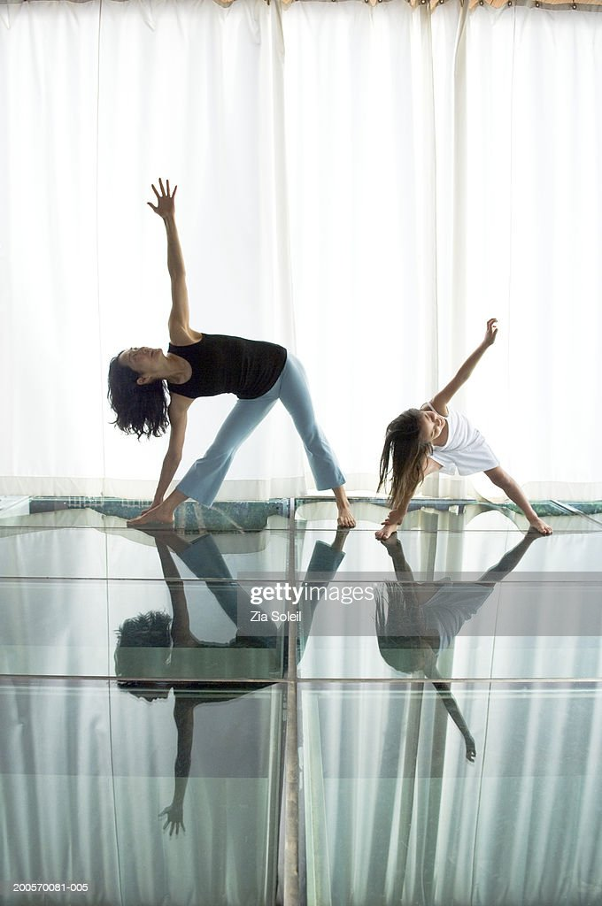 Mother with daughter (6-7) practising yoga