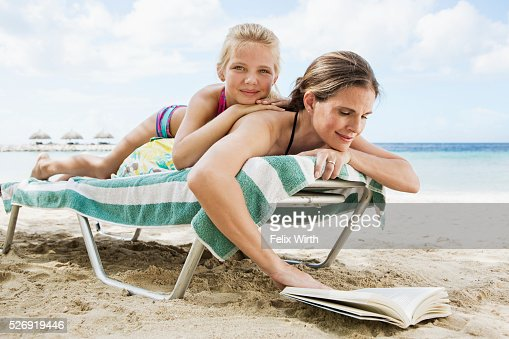 Mother with daughter (10-12) relaxing on deckchair on beach : Bildbanksbilder