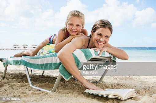 Mother with daughter (10-12) relaxing on deckchair on beach : Photo
