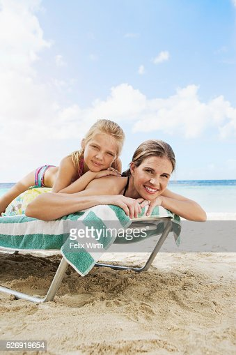 Mother with daughter (10-12) relaxing on deckchair on beach : Stock Photo