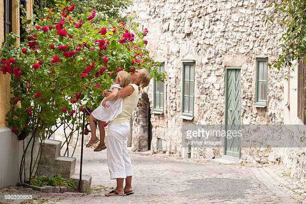 Mother with daughter smelling flowers