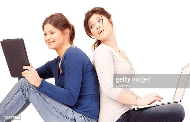 Mère et fille à l'aide d'ordinateur portable et tablette numérique sur blanc